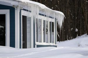 Uma casa com pingentes pendurados nos beirais em um dia de inverno com a acumulação de neve.