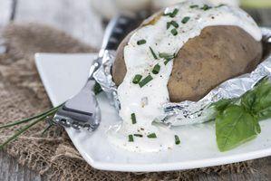 batatas assadas Top com creme azedo e cebolinha.