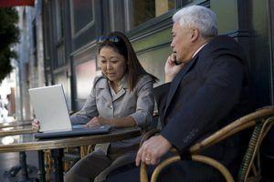 Uma mulher de negócios e homem de negócios estão trabalhando juntos em seu laptop.