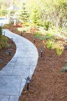 Uma passarela de azulejos acrescenta contraste com palha e plantas.