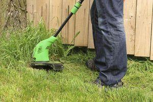 Close-up do homem que usa máquina de cortar relva em ervas daninhas.
