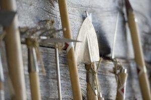 ferramentas de jardim, incluindo um garfo, enxada e pá encostada a uma parede de madeira.