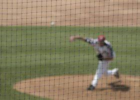 Um lançador de beisebol distante lança uma bola atrás de uma rede.